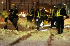 線路上にたまった雪を丁寧にかき出していく除雪作業員=27日午前0時45分、JR手稲駅付近(金田淳撮影)