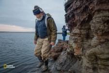 考古学者のリック・クネヒト(左)と地元のリーダーのウォーレン・ジョーンズが、解けた凍土から弓が突き出ているとの情報を受けて岸辺を調査する。「ただ流されるのを見ているつもりはありません」と、ジョーンズは言う。(Erika Larsen/National Geographic)