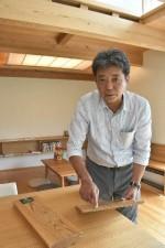 モデルハウスで合板を手に持ち、無垢材(左)との違いを説明する村田聖一社長。室内は全て無垢材が使われている