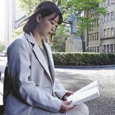 新年度から始まった講義の教科書を読む飯田さん。「進学したことで、将来をじっくり考える時間ができた」と話す(東京都新宿区で)