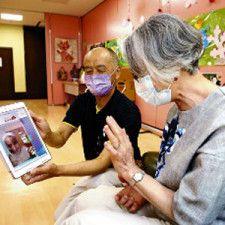 石崎さん(左)は、タブレットの画面を用いて家族と話す人のサポートも欠かさない=岩佐譲撮影