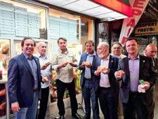 19日、米ニューヨークの路上でピザを食べるブラジルのボルソナロ大統領(左から3人目)ら=マシャド観光相のインスタグラムより、ロイター
