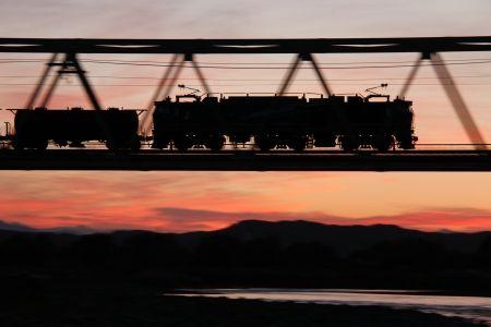 夕暮れの橋を渡る貨物列車